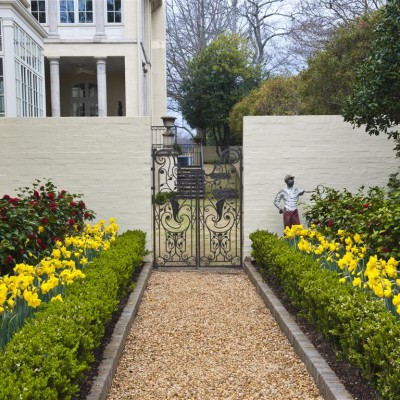 pebbled and yellow and red garden entrance leading to sculptural metal gate in residential backyard