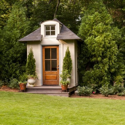 playhouse with wood door and potted garden topiaries, green landscaped lawn