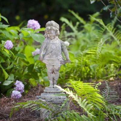 girl sculpture in fern garden next to pink hydrangeas