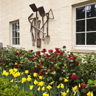 metal garden tools sculpture above yellow daffodil and red rose garden