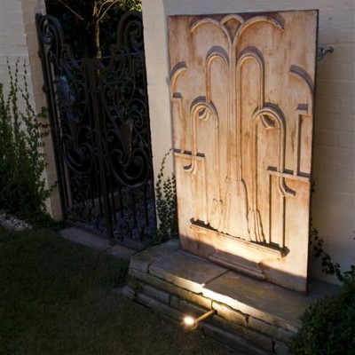 outdoor Inverted metal gate sculpture on stone against white brick wall