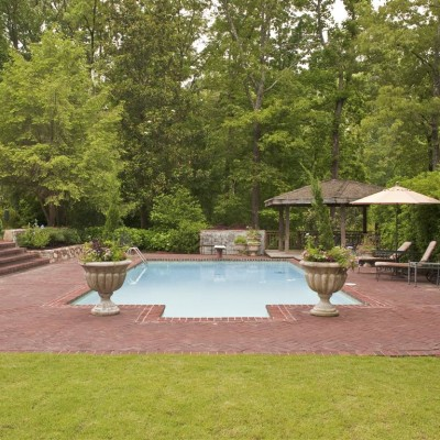 wide angle photo of red brick pool with urn potted garden surrounded by landscaped foliage