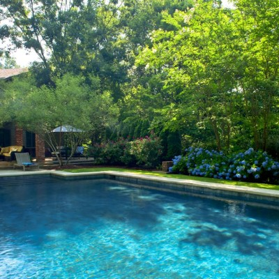 landscaped yard with hydrangeas next to residence with pool