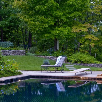 landscaped yard next to pool with stone terrace