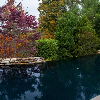 cascade style pool with stone wall in birmingham, al and fall foliage