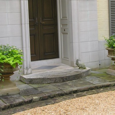 plants in footed urns on both sides of doorway