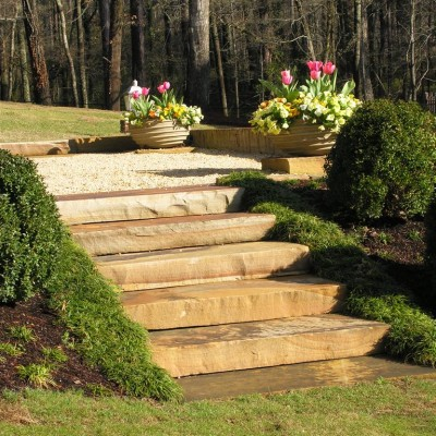 Smooth Stone Steps Leading to gravel area with Spring flowers