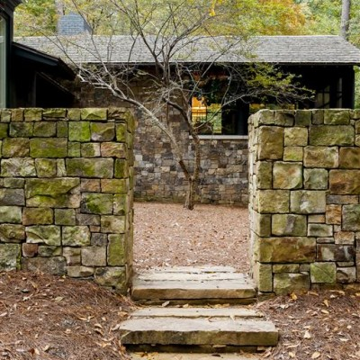 stone steps between stone wall leading to house